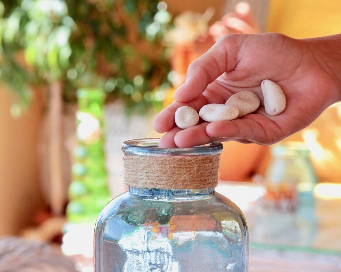 hand putting rocks in a jar